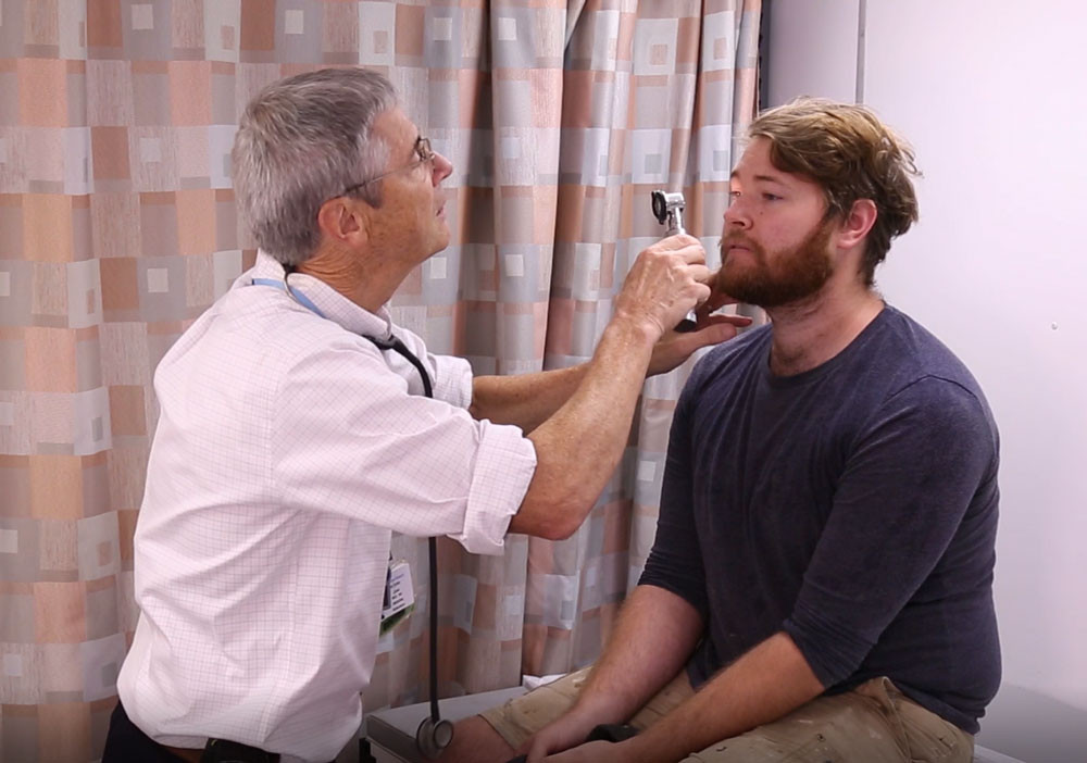Dr. giving an eye exam to a male patient.